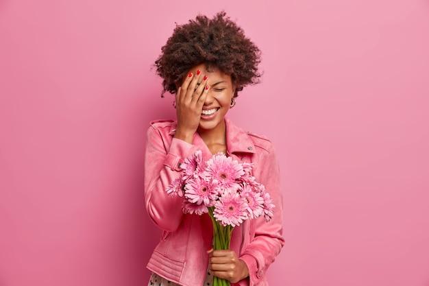 Radosna młoda afroamerykanka śmieje się radośnie, robi dłoń, dostaje fajny prezent w postaci kwiatów, trzyma piękne gerbery, wyraża szczere emocje,