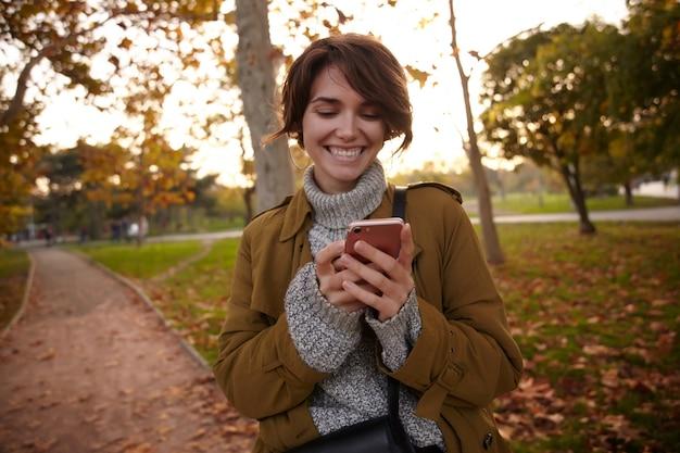 Radosna młoda atrakcyjna brunetka dama z przypadkową fryzurą, ubrana w ciepłe, przytulne ubrania, stojąc ze smartfonem w uniesionych rękach i wesoło patrząc na ekran