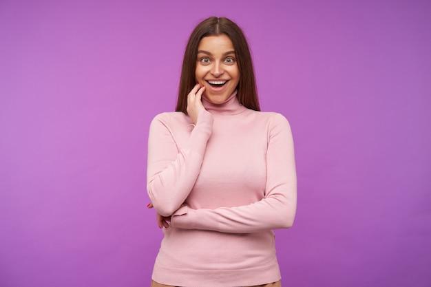 Radosna młoda atrakcyjna długowłosa brunetka dama z naturalnym makijażem trzymająca uniesioną dłoń na policzku, patrząc podekscytowana z przodu z szerokim uśmiechem, odizolowana na fioletowej ścianie