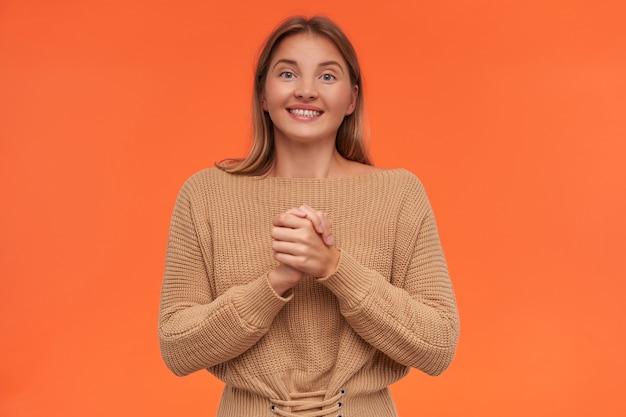 Radosna młoda atrakcyjna krótkowłosa blondynka z przypadkową fryzurą, podnosząca złożone ręce i uśmiechająca się radośnie, stojąc nad pomarańczową ścianą w beżowej bluzce