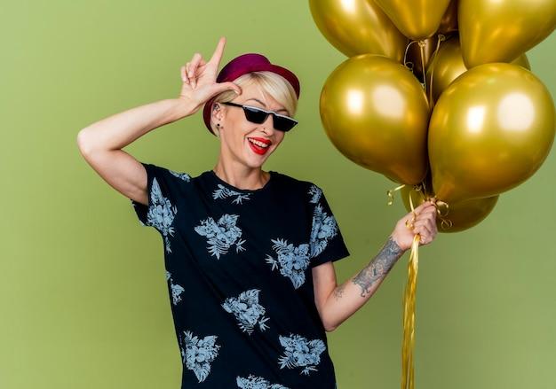 Radosna młoda blond partia kobieta ubrana w kapelusz partii i okulary przeciwsłoneczne, trzymając balony robi gest przegrany na białym tle na oliwkowej ścianie
