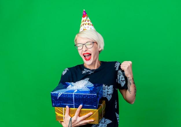 Radosna młoda blond partia kobieta w okularach i czapce urodzinowej, trzymając pudełka na prezenty, robi gest tak na białym tle na zielonej ścianie z miejsca na kopię
