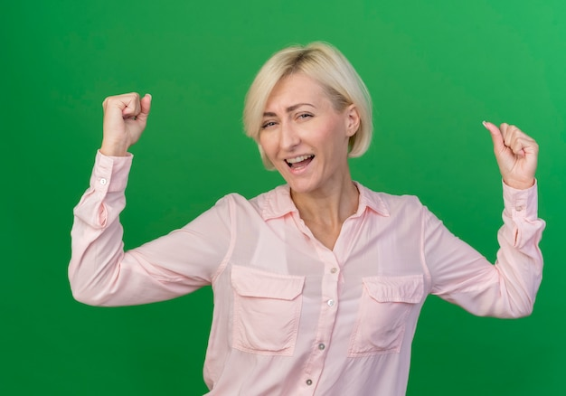 Radosna młoda blond słowiańska kobieta podnosi pięści, robi gest tak na białym tle na zielonym tle