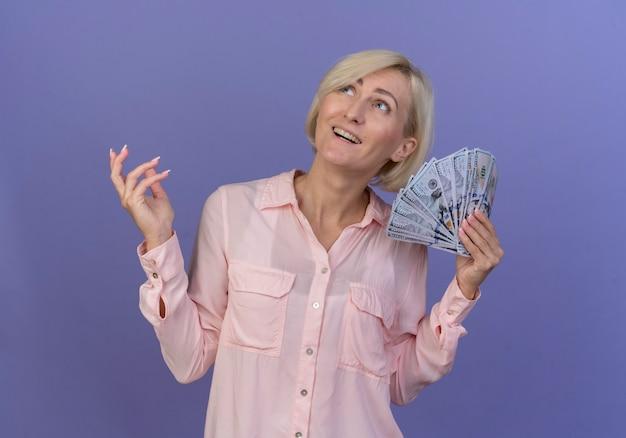 Radosna młoda blond słowiańska kobieta trzyma pieniądze trzymając rękę w powietrzu i patrząc w górę na białym tle na fioletowym tle