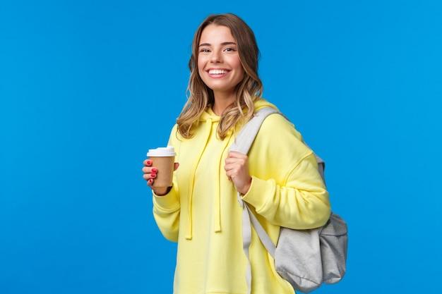 Radosna młoda blond studentka z plecakiem uśmiechnięta kamera zadowolona jak trzyma kubek kawy na wynos