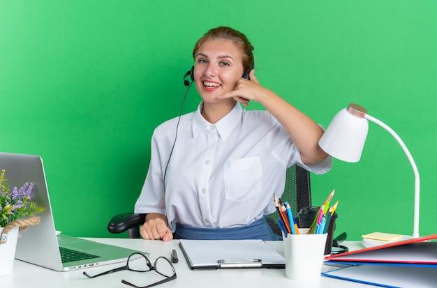 Radosna młoda blondynka call center dziewczyna nosi zestaw słuchawkowy, siedząc przy biurku z narzędziami do pracy, wykonując gest połączenia
