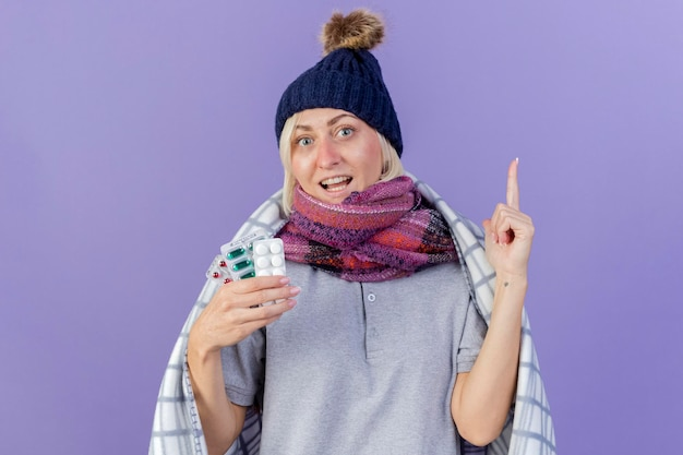 Radosna młoda blondynka chora słowiańska kobieta w czapce zimowej