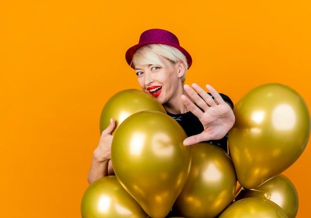 Radosna młoda blondynka imprezowa dziewczyna w kapeluszu imprezowym stojąca za balonami chwytająca jednego z nich robi gest zatrzymania na aparat patrząc w kamerę odizolowaną na pomarańczowym tle