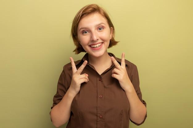 Radosna młoda blondynka patrząca na przód robi znak pokoju na oliwkowozielonej ścianie z kopią miejsca