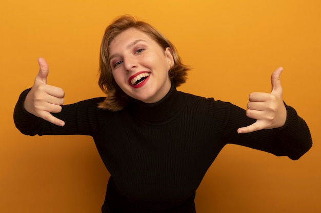 Radosna młoda blondynka patrząca z przodu, wykonująca luźny gest na pomarańczowej ścianie