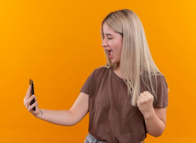 Radosna młoda blondynka robi selfie z podniesioną pięścią i zamkniętymi oczami na odizolowanej pomarańczowej przestrzeni