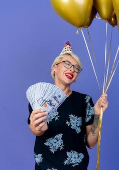Radosna młoda blondynka strony w okularach i czapkę urodzinową, trzymając balony i pieniądze, patrząc na bok na białym tle na fioletowym tle