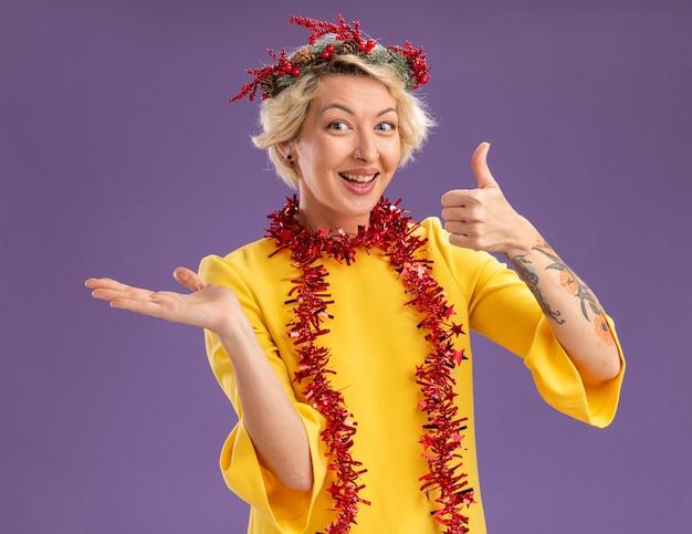 Radosna młoda blondynka ubrana w świąteczny wieniec na głowę i świecącą girlandę wokół szyi patrząc na kamerę pokazującą pustą dłoń i kciuk w górę na białym tle na fioletowym tle