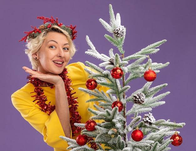 Radosna młoda blondynka ubrana w świąteczny wieniec na głowę i świecącą girlandę wokół szyi, stojąca za udekorowaną choinką, patrząc na kamerę, trzymając rękę pod głową odizolowaną na fioletowym tle