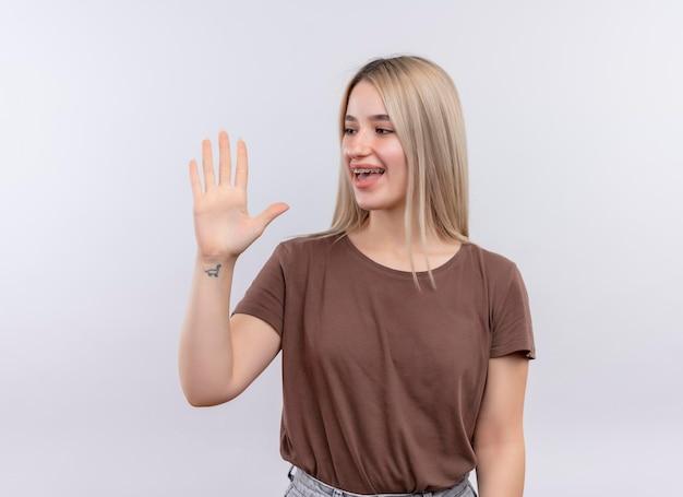 Radosna młoda blondynka w aparatach ortodontycznych pokazując pięć ręką i patrząc na to na pojedyncze białe miejsce z miejsca na kopię