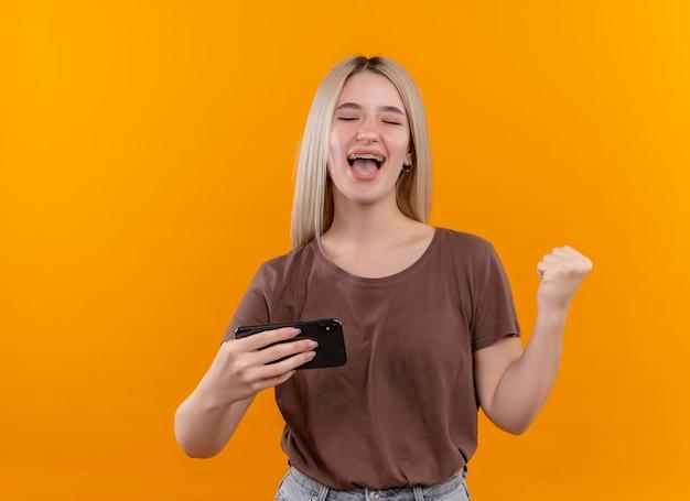 Radosna młoda blondynka w aparatach ortodontycznych trzymając telefon komórkowy z podniesioną pięścią i zamkniętymi oczami na odizolowanej pomarańczowej przestrzeni z miejsca na kopię