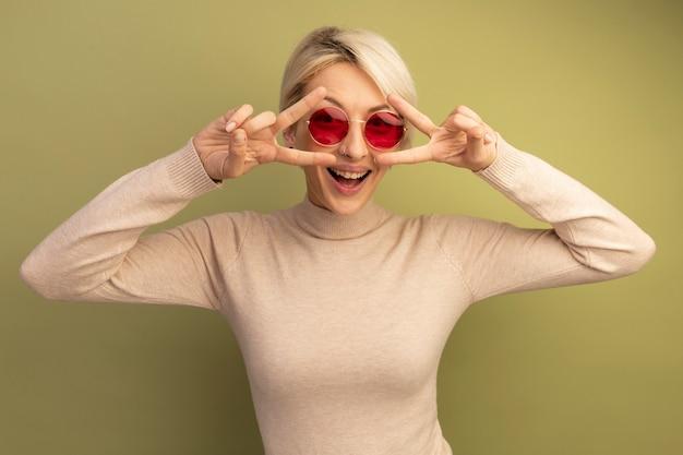 Radosna młoda blondynka w okularach przeciwsłonecznych pokazujących symbole znaku v w pobliżu oczu