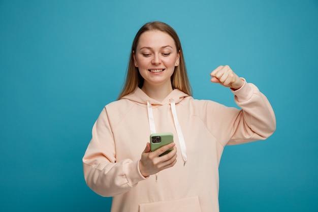 Radosna młoda blondynki kobieta robi tak gestowi i patrząc na telefon komórkowy