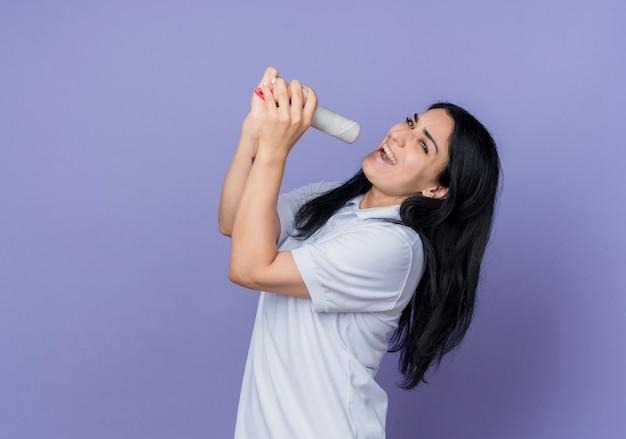 Radosna młoda brunetka dziewczynka kaukaski trzyma pędzel udając, że śpiewa, patrząc na białym tle na fioletowej ścianie