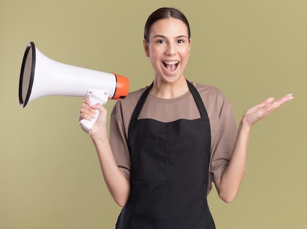Radosna młoda brunetka fryzjerka w mundurze trzyma rękę otwartą i trzyma głośny głośnik na oliwkowozielonej ścianie z miejscem na kopię