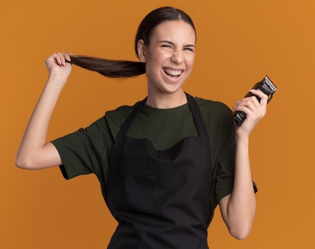 Radosna młoda brunetka fryzjerka w mundurze trzyma warkocz i maszynkę do strzyżenia włosów odizolowaną na pomarańczowej ścianie z miejscem na kopię