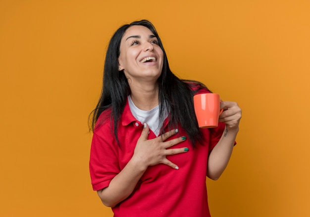 Radosna młoda brunetka kaukaski dziewczyna ubrana w czerwoną koszulę kładzie rękę na piersi i trzyma kubek patrząc z boku na białym tle na pomarańczowej ścianie