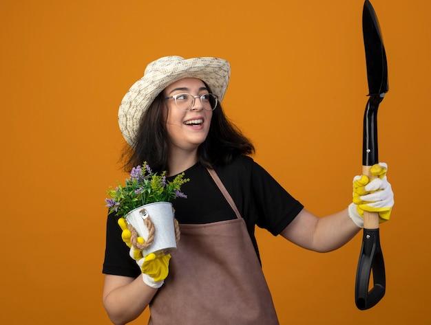 Radosna młoda brunetka ogrodniczka w okularach optycznych i mundurze w kapeluszu ogrodniczym i rękawiczkach trzyma doniczkę i patrzy na łopatę odizolowaną na pomarańczowej ścianie