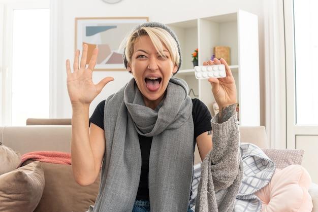 Radosna młoda, chora słowiańska kobieta z szalikiem na szyi, w czapce zimowej, trzymająca blistry z lekarstwami i podnosząca rękę do góry, siedząc na kanapie w salonie