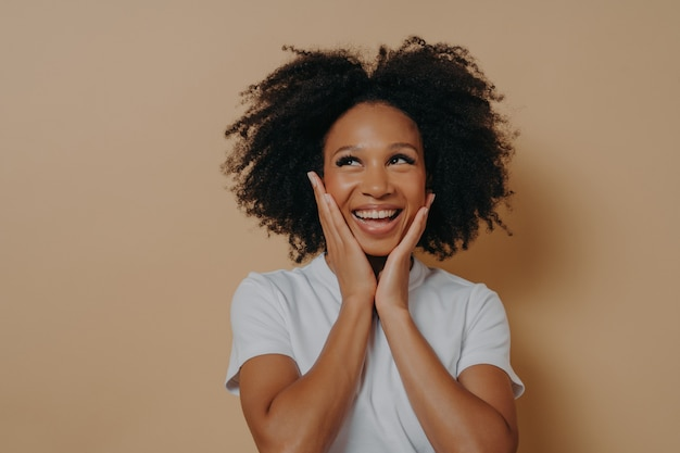 Radosna młoda ciemnoskóra kobieta czuje się szczęśliwa, uśmiecha się do kamery i dotyka policzków obiema rękami, beztroska afrykańska kobieta w białej koszulce wyrażająca pozytywność, pozuje na białym tle na beżowym tle