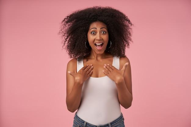 Radosna młoda ciemnoskóra kobieta z przypadkową fryzurą, trzymająca dłonie na piersi z szerokim szczęśliwym uśmiechem, odizolowana na różowo