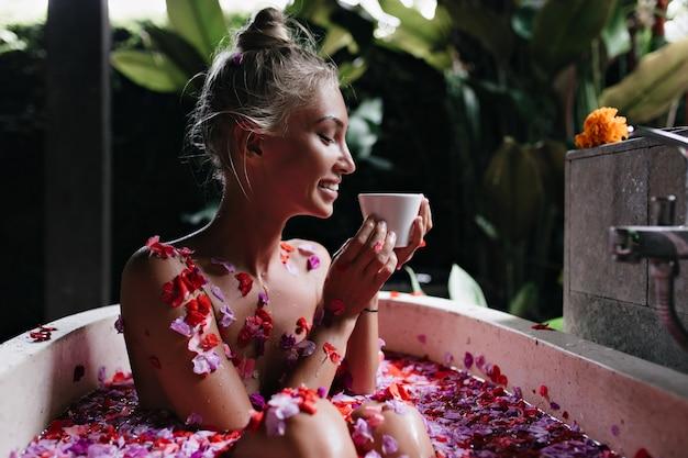 Radosna młoda dama relaksując się podczas porannego spa i pijąc smaczną herbatę. ujmująca modelka z krwistymi włosami, uśmiechając się podczas kąpieli w weekend.