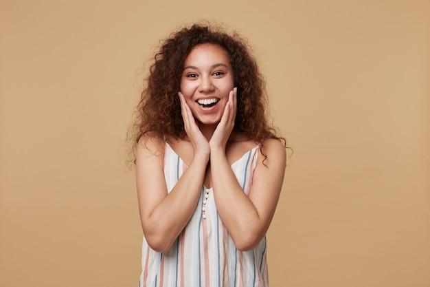 Radosna młoda, długowłosa, kręcona kobieta z naturalnym makijażem, trzymająca twarz z podniesionymi dłońmi i wyglądająca szczęśliwie, odizolowana na beżu