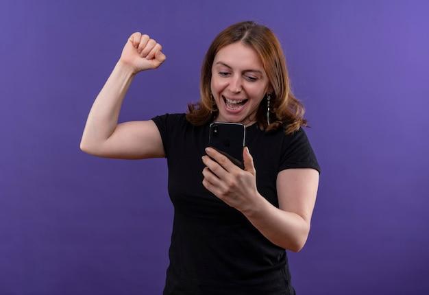 Radosna młoda dorywczo kobieta trzyma telefon komórkowy z podniesioną pięścią na odosobnionej fioletowej przestrzeni z miejsca na kopię