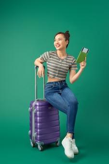 Radosna młoda dziewczyna azjatyckich siedzi na walizce i trzyma paszport, bilet lotniczy do podróży na zielono.