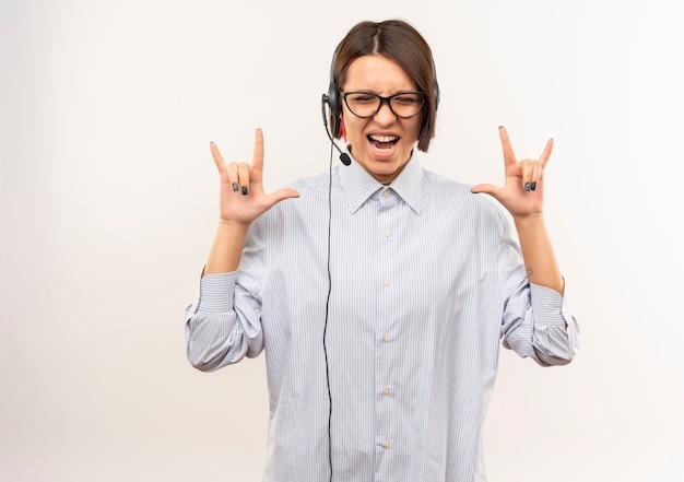 Radosna młoda dziewczyna call center w okularach i zestaw słuchawkowy robi rockowe znaki z zamkniętymi oczami na białym tle