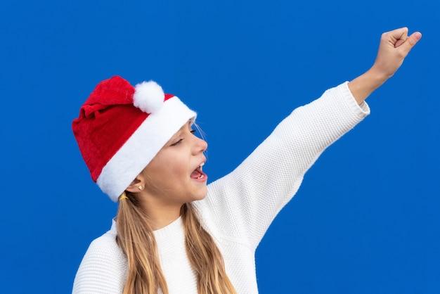 Radosna młoda dziewczyna gestykuluje w santa kapeluszu.