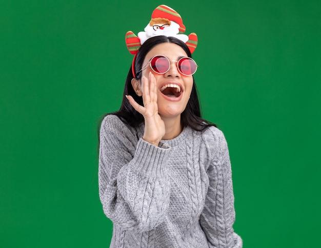 Radosna młoda dziewczyna kaukaska ubrana w opaskę świętego mikołaja w okularach patrząc na aparat, szepcząc na białym tle na zielonym tle
