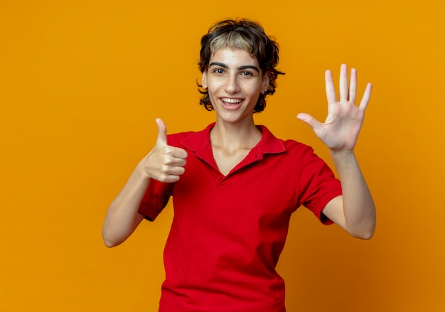 Radosna młoda dziewczyna kaukaska z fryzurą pixie pokazująca sześć z rękami odizolowanymi na pomarańczowym tle z miejsca na kopię