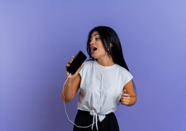 Radosna młoda dziewczyna kaukaski na słuchawkach trzyma telefon, udając, że śpiewa, patrząc na bok