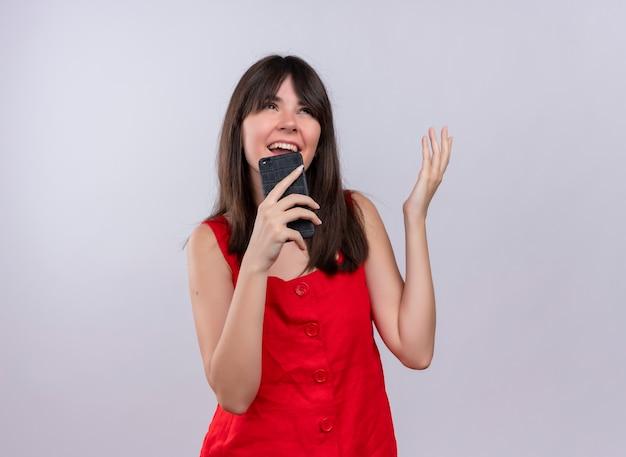 Radosna młoda dziewczyna kaukaski trzymając telefon i podnosząc rękę patrząc na kamery na na białym tle z miejsca na kopię
