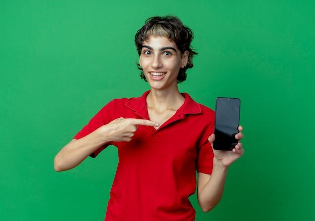 Radosna młoda dziewczyna kaukaski z fryzurą pixie, trzymając i wskazując na telefon komórkowy na białym tle na zielonym tle