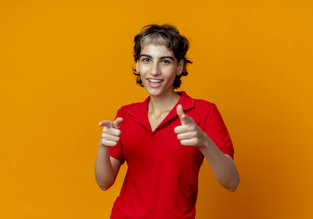 Radosna młoda dziewczyna kaukaski z fryzurą pixie, wskazując na aparat na białym tle na pomarańczowym tle z miejsca na kopię