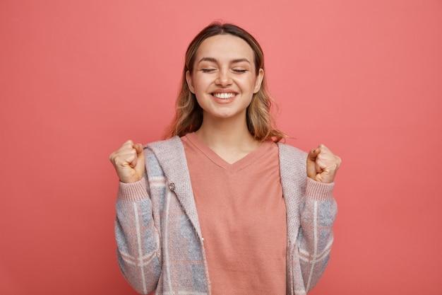 Radosna młoda dziewczyna robi tak gest z zamkniętymi oczami