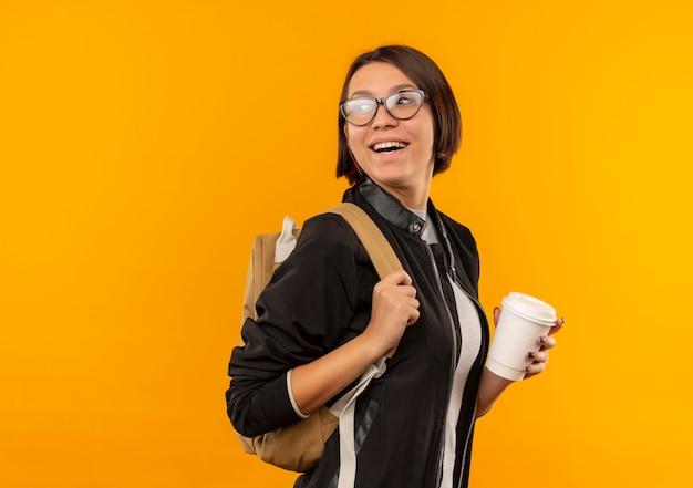 Radosna młoda dziewczyna studenta w okularach iz powrotem worek stojący w widoku profilu patrząc za trzymając filiżankę kawy na białym tle na pomarańczowo