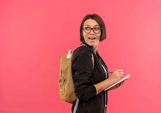 Radosna młoda dziewczyna studentka w okularach i plecak stojący w widoku profilu trzymając pióro i notes patrząc za na białym tle na różowo