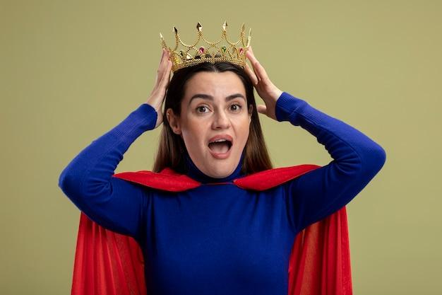 Radosna młoda dziewczyna superbohatera zakładając koronę na głowę na białym tle na oliwkową zieleń
