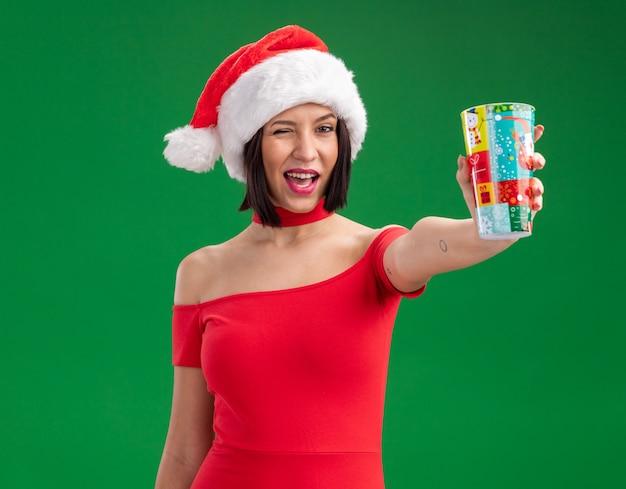 Radosna młoda dziewczyna ubrana w santa hat wyciągając plastikowy kubek bożonarodzeniowy mrugając na białym tle na zielonej ścianie