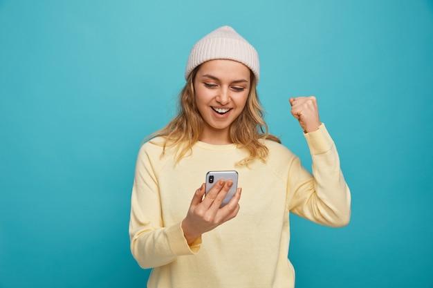 Radosna młoda dziewczyna ubrana w zimowy kapelusz, trzymając i patrząc na telefon komórkowy robi tak gestowi