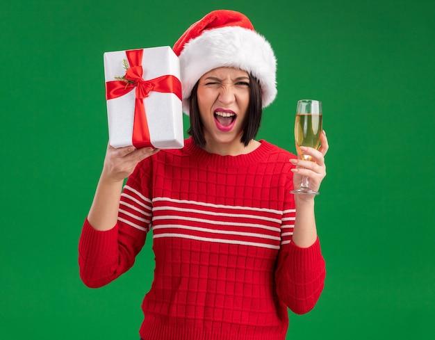 Radosna młoda dziewczyna w czapce mikołaja trzymająca prezent w pobliżu głowy i kieliszek szampana patrząc na aparat mrugający na białym tle na zielonym tle