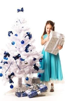 Radosna młoda dziewczyna w niebieskiej sukience trzyma prezent w dłoniach i ozdabia noworoczną białą sztuczną choinkę na białej ścianie